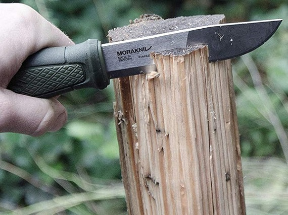 Cutting wood with survival knife