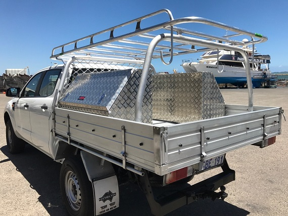picture of a white ute with roof racks on a parking beside a boat