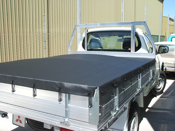 picture of a white Mitsubishi Ute with aluminum tray tonneau cover on a parking beside warehouse