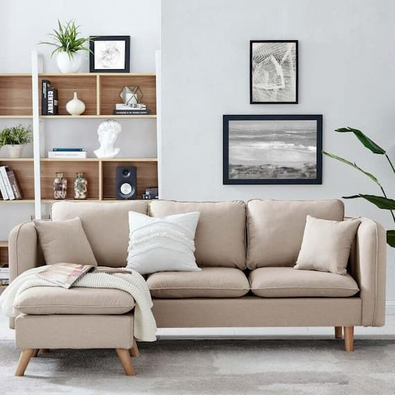 beige sofa bed for living room with ottoman and white thorw on it and a magazine