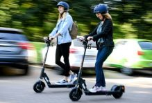 two girls driving scooters